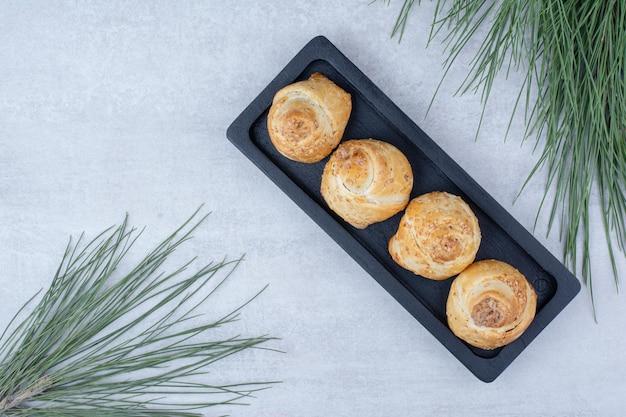 Запеченные сладкие булочки на черной тарелке с веткой сосны. фото высокого качества