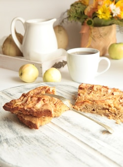 백그라운드에서 사과와 차 컵과 함께 구운된 맛있는 사과 파이. 집에서 만든 건강 식품 개념입니다.