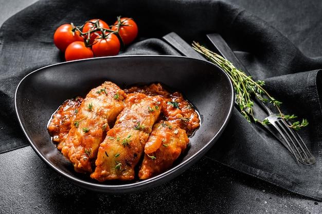 皿の上のトマトでティラピア魚を焼きました。黒の背景。上面図