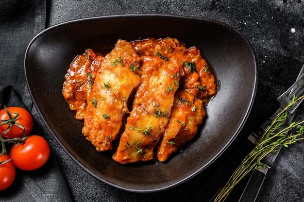 プレート上のトマトで焼いたティラピアの魚。黒の背景。上面図。