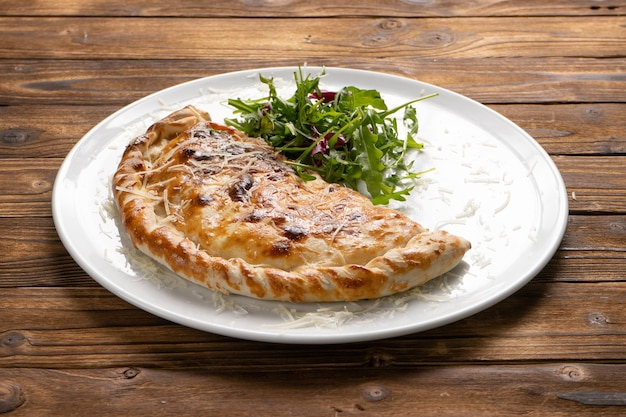 木製のキッチンテーブルの白いセラミックプレートに新鮮なルッコラとパルメザンチーズを添えて、パリッとした茶色のピザカルツォーネに焼き上げました。