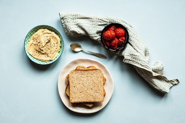 Baked tomatoes, hummus and bread. a beige towel and a spoon. blue surface. top view horizontal image.