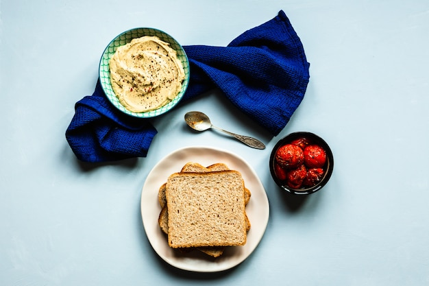 Baked tomatoes, hummus and bread. a deep blue towel and a spoon. blue surface. top view horizontal image.