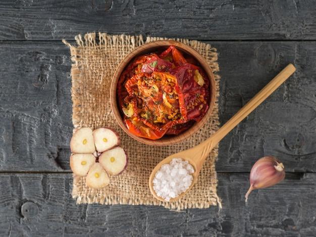 Запеченные помидоры в деревянной миске деревянной ложкой на куске мешковины