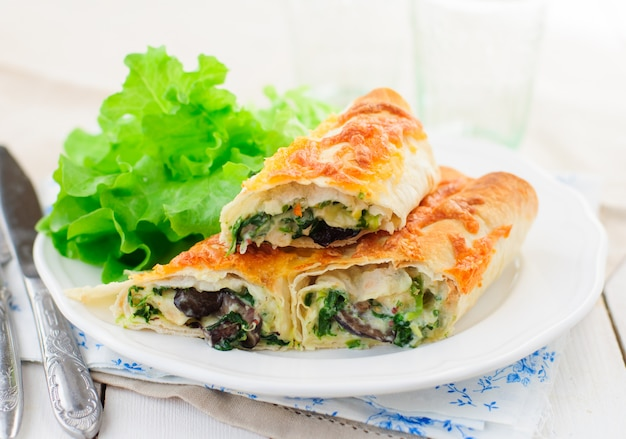 Baked tortilla rolls with spinach, chicken and mushrooms