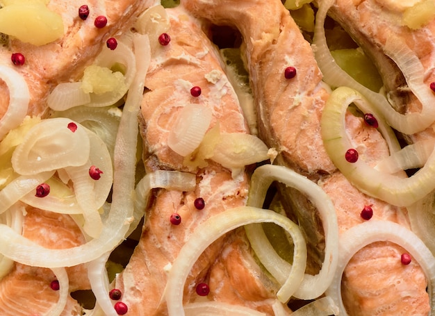 Baked trout pieces with onions, potatoes and pink peppers, background