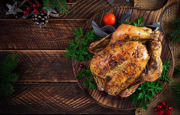 Baked turkey or chicken. the christmas table is served with a turkey, decorated with bright tinsel. fried chicken, table setting. christmas dinner. top view, overhead, copy space