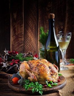 Baked turkey or chicken. the christmas table is served with a turkey, decorated with bright tinsel. fried chicken, table setting. christmas dinner.