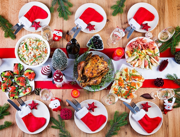 Tacchino al forno. cena di natale. la tavola di natale è servita con un tacchino, decorato con orpelli luminosi e candele. pollo fritto, tavola. cena di famiglia. vista dall'alto, disteso, sovraccarico, copia dello spazio