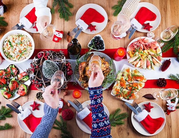 Tacchino al forno. cena di natale. la tavola di natale è servita con un tacchino, decorato con orpelli luminosi e candele. pollo fritto, tavola. cena di famiglia. vista dall'alto, mani nel telaio
