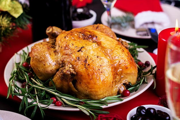 Baked turkey. christmas dinner. the christmas table is served with a turkey, decorated with bright tinsel and candles. fried chicken, table.  family dinner.