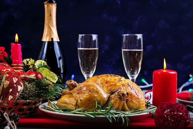 Baked turkey. the christmas table is served with a turkey, decorated with bright tinsel