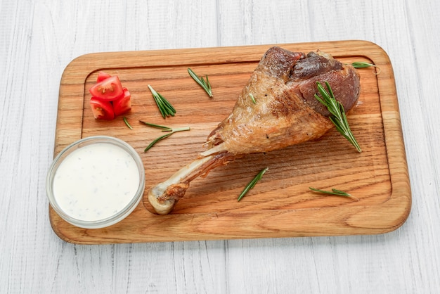 Baked turkey ham with sauce on wooden surface