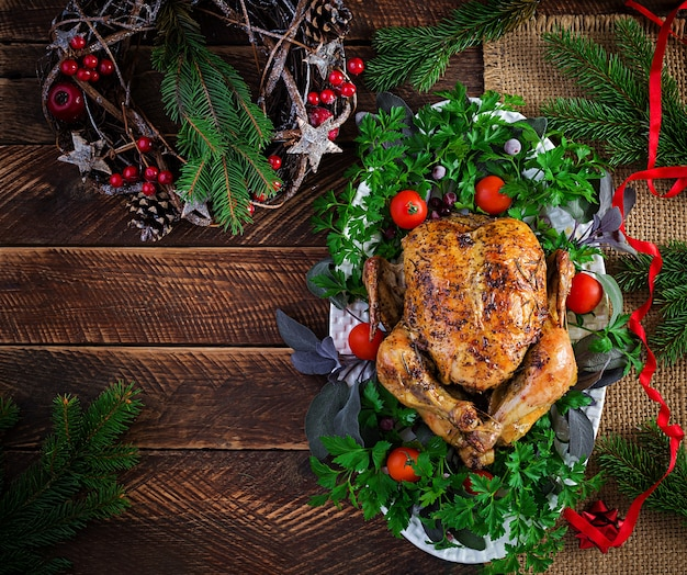 焼きたての七面鳥または鶏肉。クリスマステーブルには、明るい見掛け倒しで飾られた七面鳥が添えられています。フライドチキン、テーブルセッティング。クリスマスディナー。上面図、オーバーヘッド、コピースペース