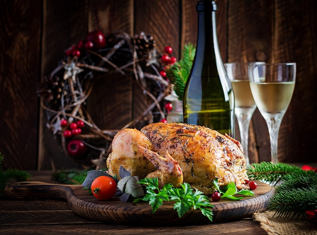 焼きたての七面鳥または鶏肉。クリスマステーブルには、明るい見掛け倒しで飾られた七面鳥が添えられています。フライドチキン、テーブルセッティング。クリスマスディナー。