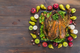 Baked turkey with fruits on table