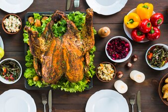 Baked turkey with plates on table