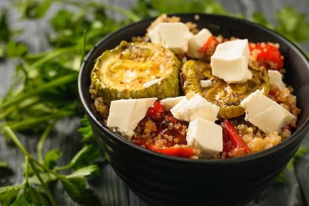 黒いテーブルにキノアとチーズの焼き野菜サラダ。焼き野菜のサラダとボウルに鉄のフォーク。上から見た図。フラット横たわっていた。