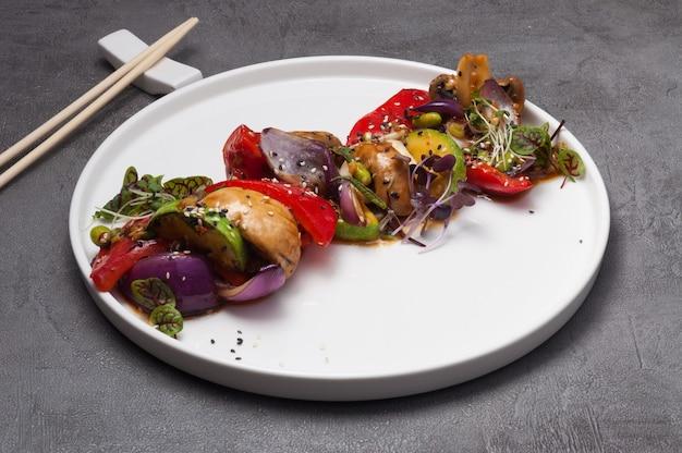 Запеченные овощи и грибы на белой тарелке