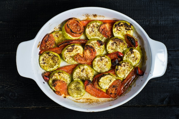 Baked vegetables in baking dish, zucchini, bell pepper and zucchini.