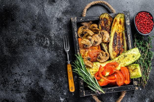 Запеченные овощи болгарский перец, цукини, баклажаны и помидоры в деревянном подносе. черный деревянный фон. вид сверху. скопируйте пространство.