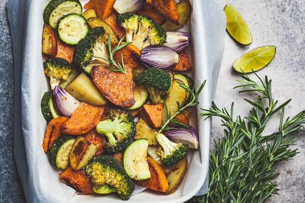 オーブン皿、トップビューで焼き野菜。焼き芋、ズッキーニ、ブロッコリー。健康的なビーガンフードのコンセプトです。