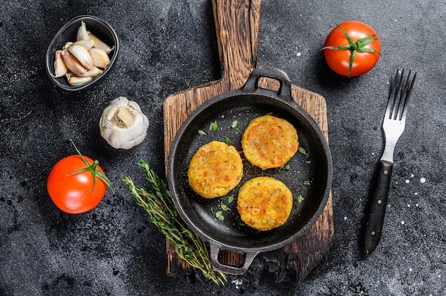 ビーガンバーガー用の焼き野菜パテカツレツ。暗いテーブル。上面図。