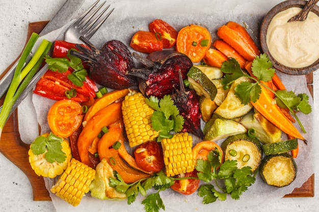 Baked vegetables: pumpkin, beets, carrots, peppers, zucchini and corn on wooden board.