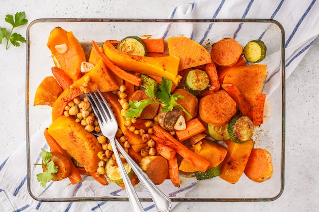 Baked vegetables with chickpeas in glass dish, top view.