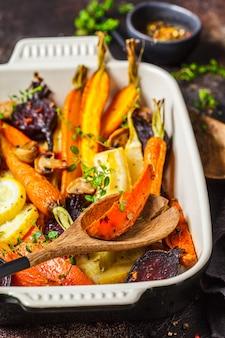 Запеченные овощи с тимьяном в духовке блюдо, темный фон.
