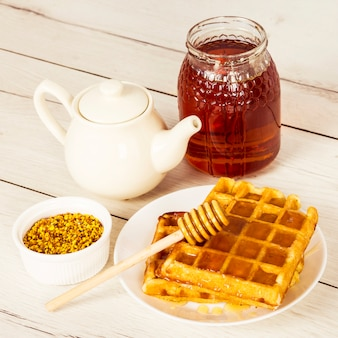 Baked waffle; honey; teapot and bee pollen on wooden table
