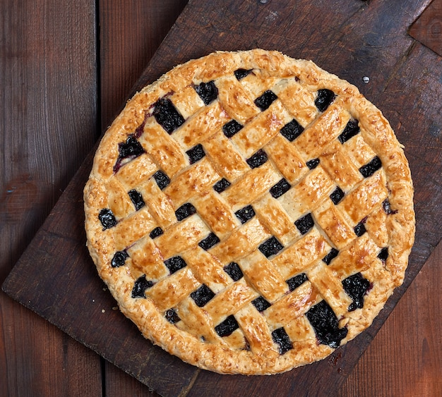 Baked whole black currant pie lay on a brown wooden cutting board