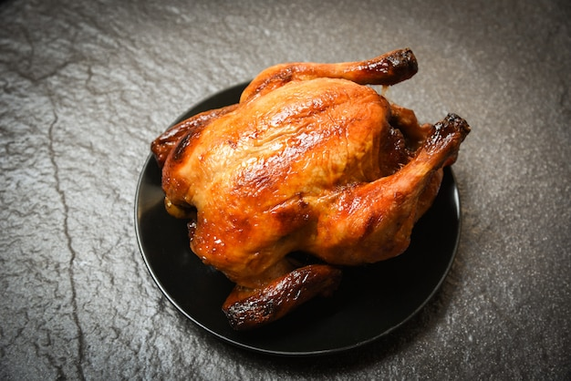 Baked whole chicken grilled on black plate