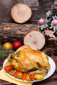 Baked whole chicken with a garnish of potatoes and tomatoes on a plate, christmas decoration