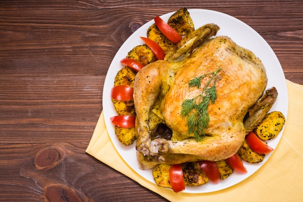 Baked whole chicken with a garnish of potatoes and tomatoes on a plate, top view
