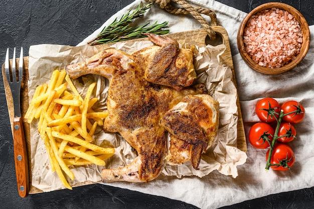 Запеченная целая курица с картофелем. черный фон. вид сверху
