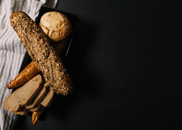 Baked whole grain breads on black dark background