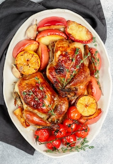 Baked whole little chickens with apples, lemon, garlic, thyme, tomatoes and spices