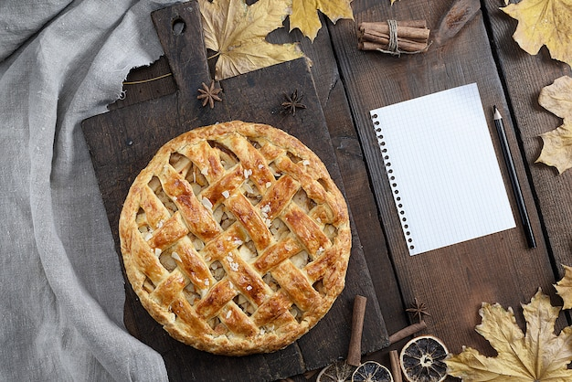 Baked whole round apple pie on a brown wooden board, puff pastry