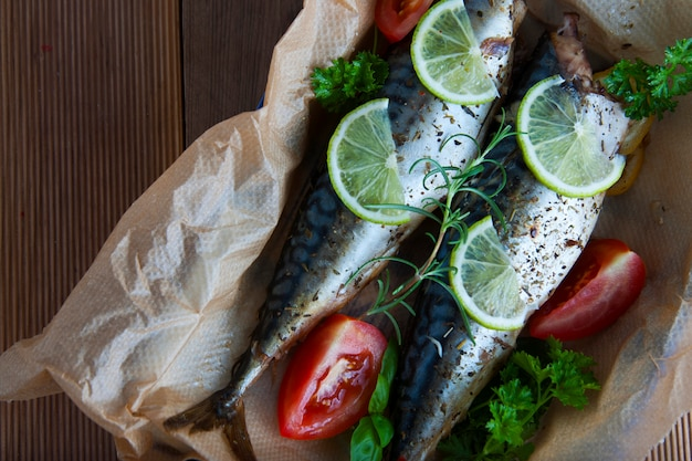 Baked whole sea fishes on baking paper with lemon and herbs.