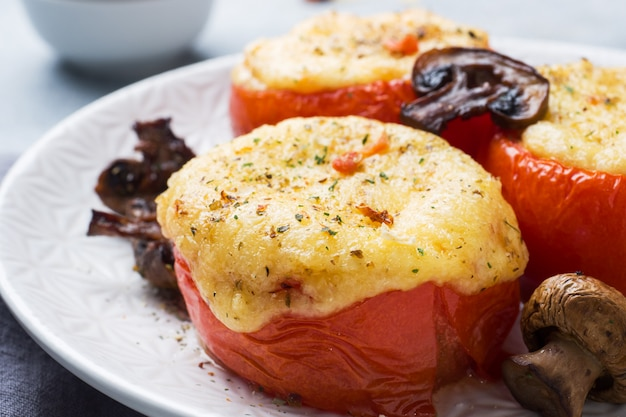 Baked whole tomatoes stuffed with mushrooms and cheese with spices. close up selective focus