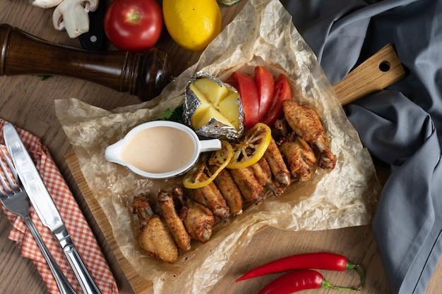 Запеченные с лимоном куриные крылышки с сырным соусом, запеченные в фольге овощи и картофель