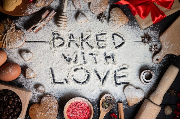 Baked with love written on flour. gingerbread heart shaped cookies, spices, coffee beans and baking supplies on black wood background