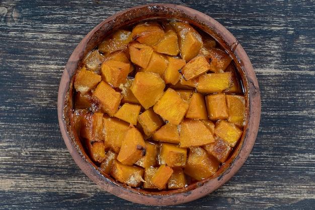 나무 탁자에 있는 접시에 꿀, 올리브 오일, 향신료를 넣은 구운 노란색 호박. 채식주의 자 음식. 확대