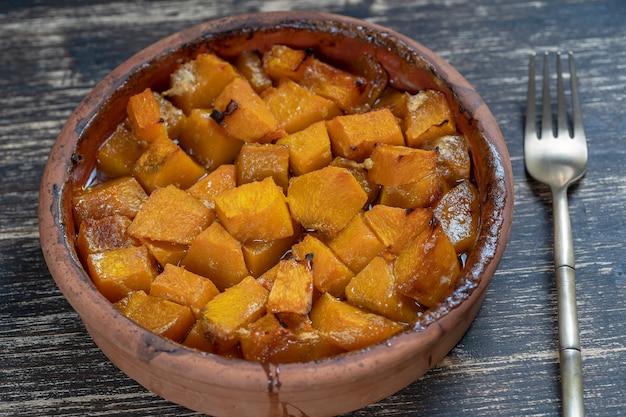 Запеченная желтая тыква с медом, оливковым маслом и специями на тарелке на деревянном столе. вегетарианская пища. закрыть вверх