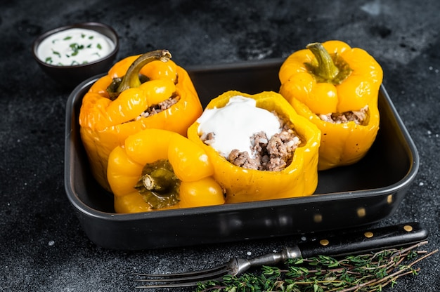 Baked yellow sweet bell pepper stuffed with beef meat, rice and vegetables. black background. top view.