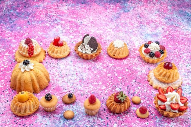 Запеченные вкусные пирожные со сливками вместе с разными ягодами на светлом-ярком столе, бисквитный ягодный сладкий запеканный чай