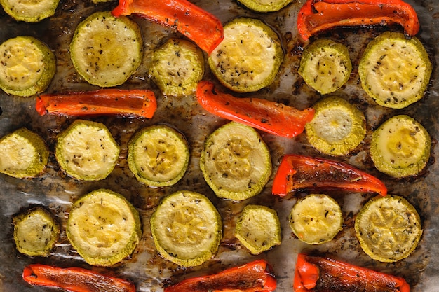 Baked zucchini and red bell pepper on a baking sheet.