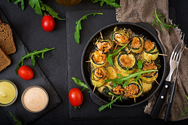 Baked zucchini rolls with cheese, carrot and chicken breast. flat lay. top view