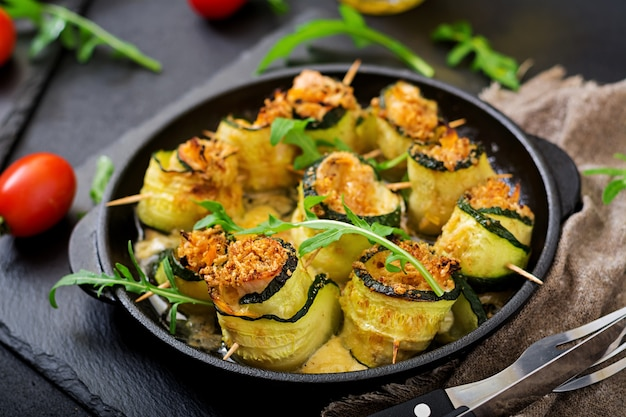 Baked zucchini rolls with cheese, carrot and chicken breast